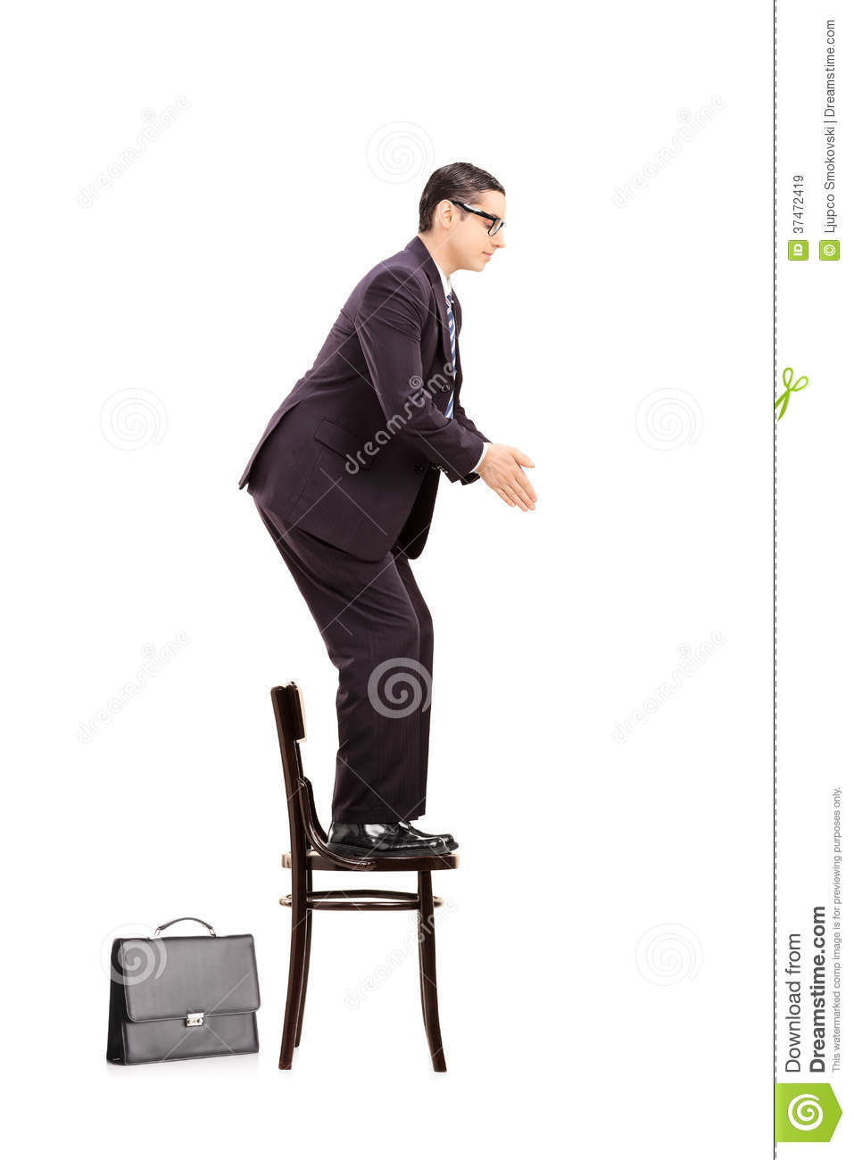 Male Businessman Standing Up On Chair Ready To Jump ...