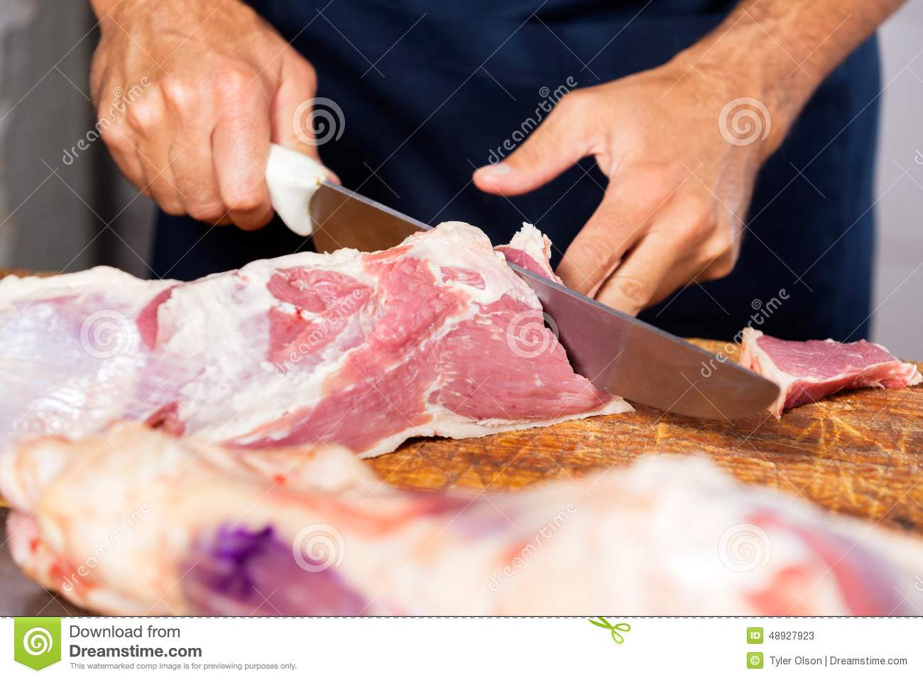 male butcher cutting raw meat with knife stock image image 48927923. Black Bedroom Furniture Sets. Home Design Ideas