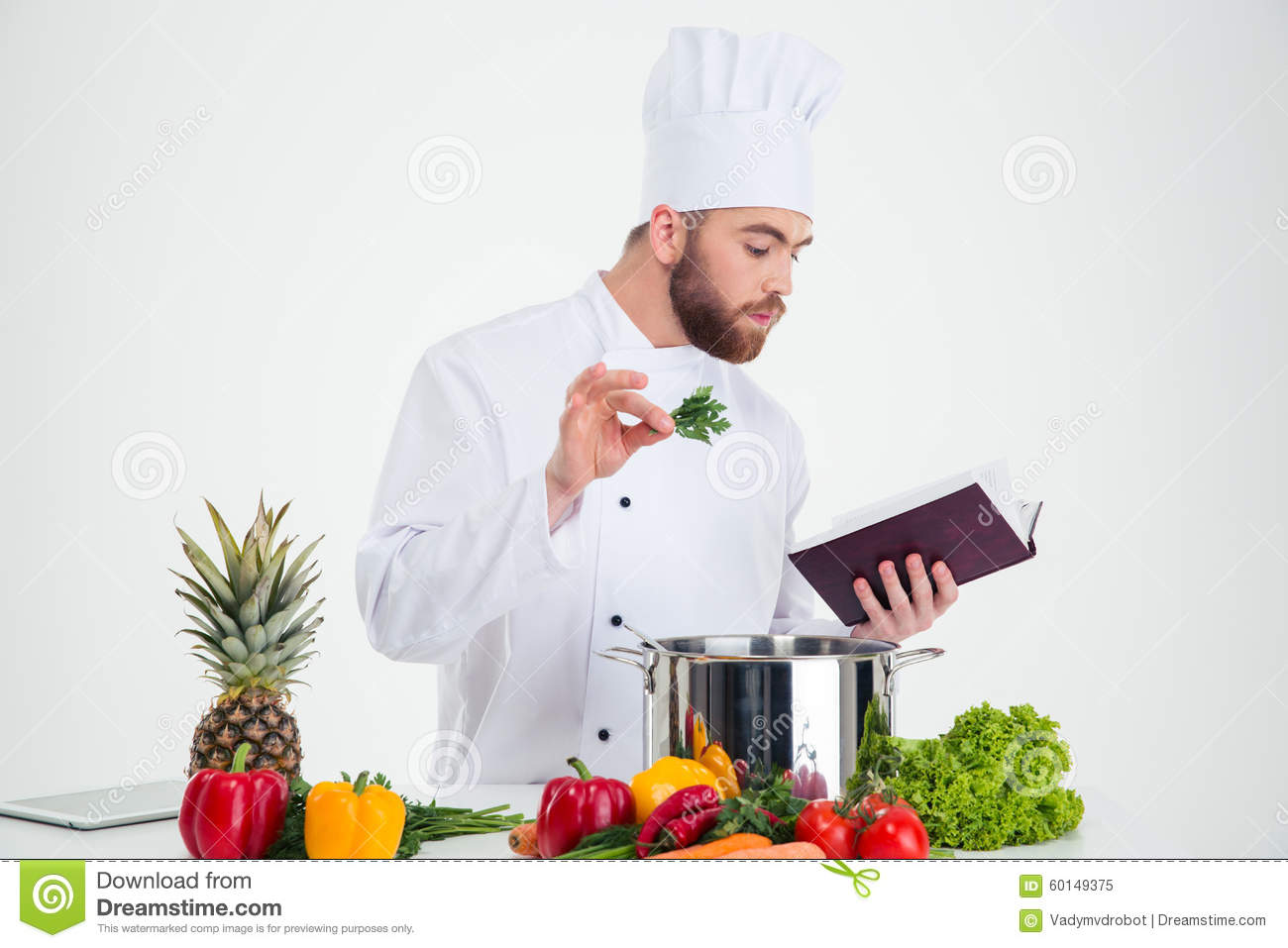 Male Chef Cook Reading Recipe Book While Preparing Food