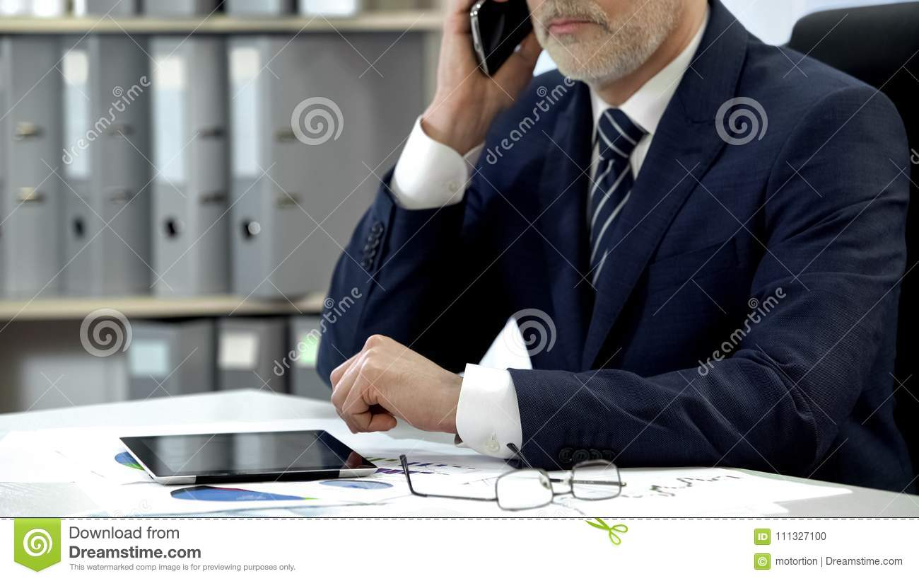 Male company director dialing, talking cell phone, tablet and glasses on table
