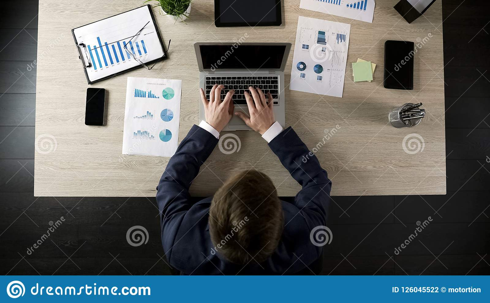 Male company director typing on laptop, planning project or business strategy