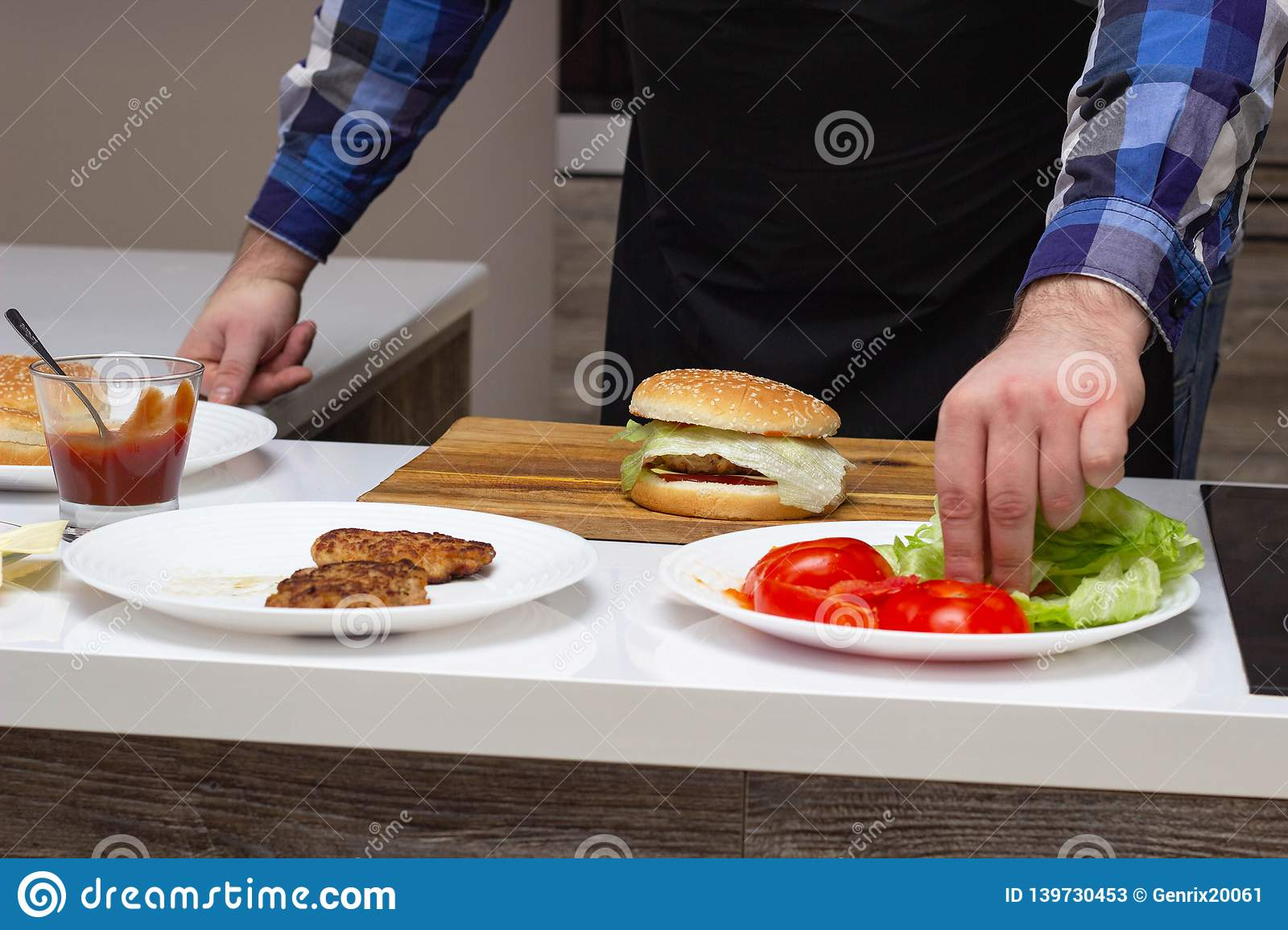 Male cook preparing cheeseburgers and hamburgers in the kitchen, on the table are the ingredients