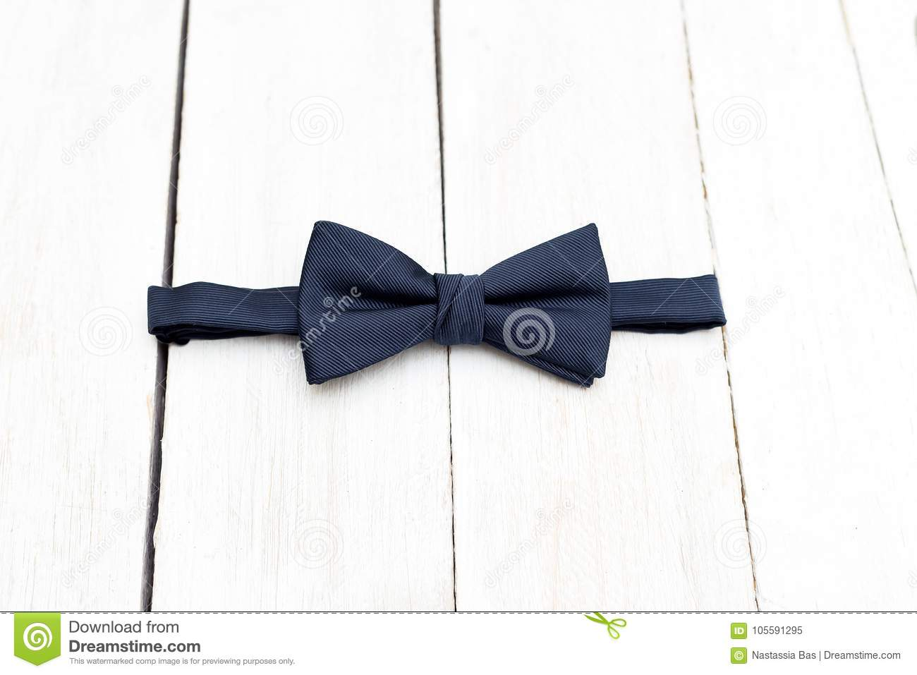 Male dark blue bow tie on a wooden background. Elements of style
