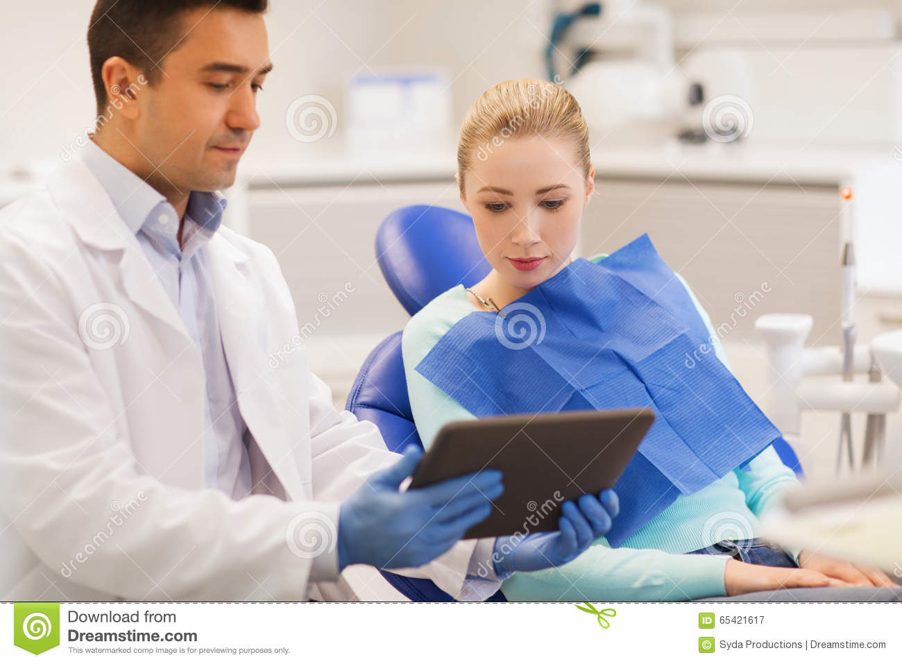 health care concept  male dentist showing tablet pc computer to women