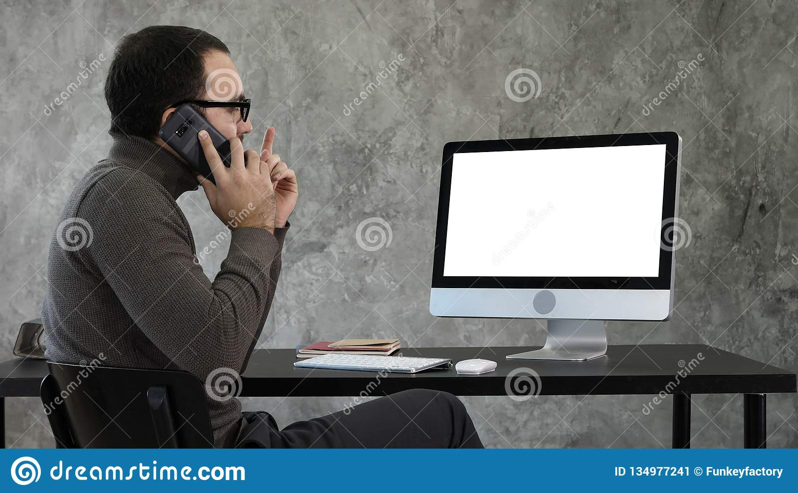 Male Designer Working At Computer In Contemporary Office. He talks on the phone and looking on what is on the screen