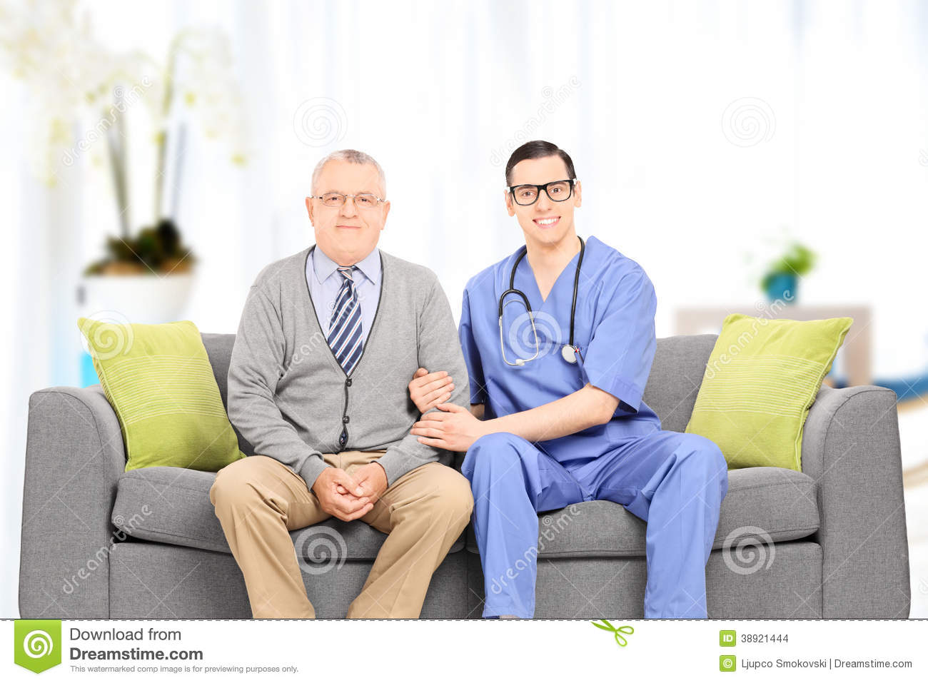 Male Doctor And Elderly Gentleman Seated On Sofa Stock