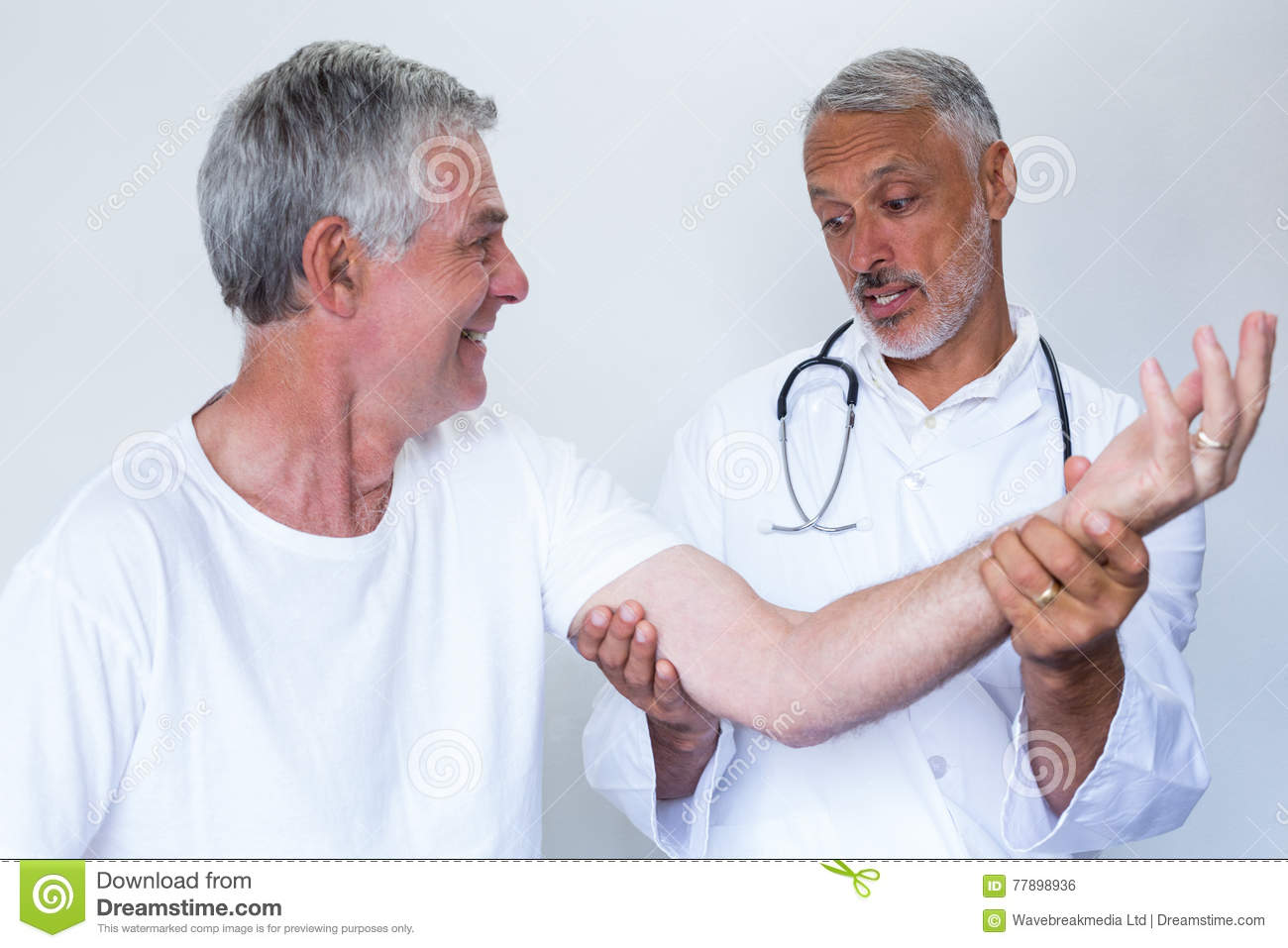 Male Doctor Giving Palm Acupressure Treatment To Senior ...