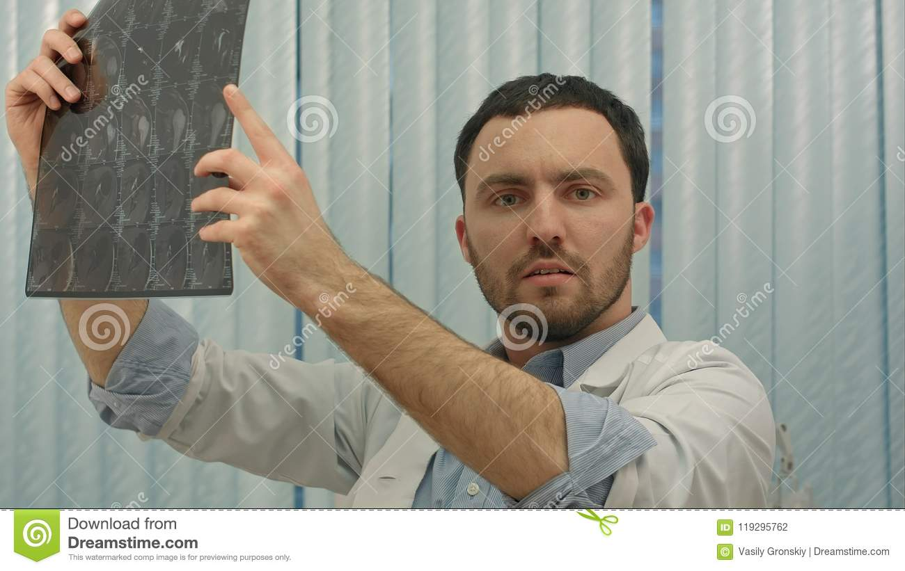 Male doctor looking with humorous shock at x ray
