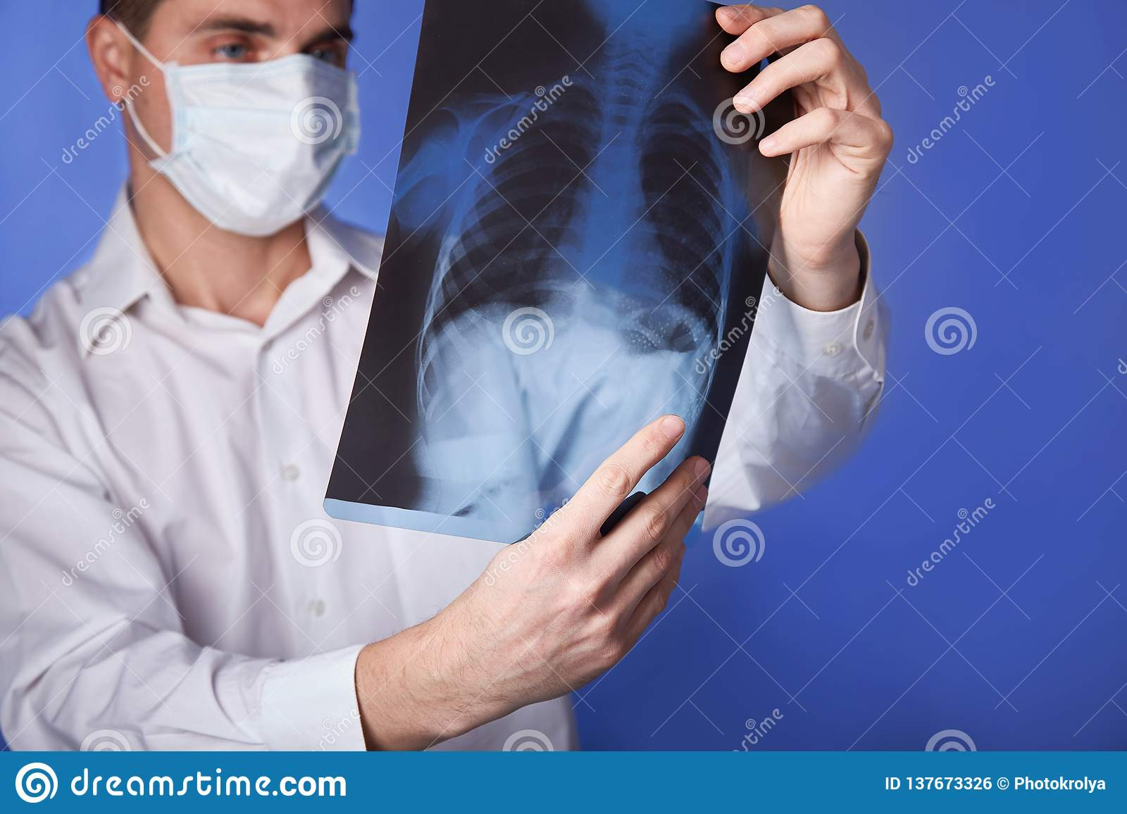 Male doctor in mask and white coat holding x-ray or roentgen of lungs, fluorography, image on blue background