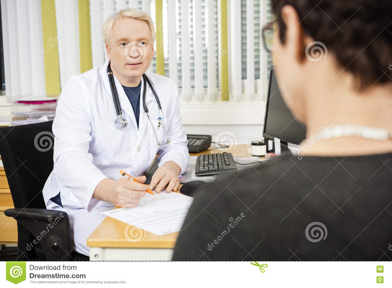 Male Doctor Writing Prescription For Female Patient At Desk