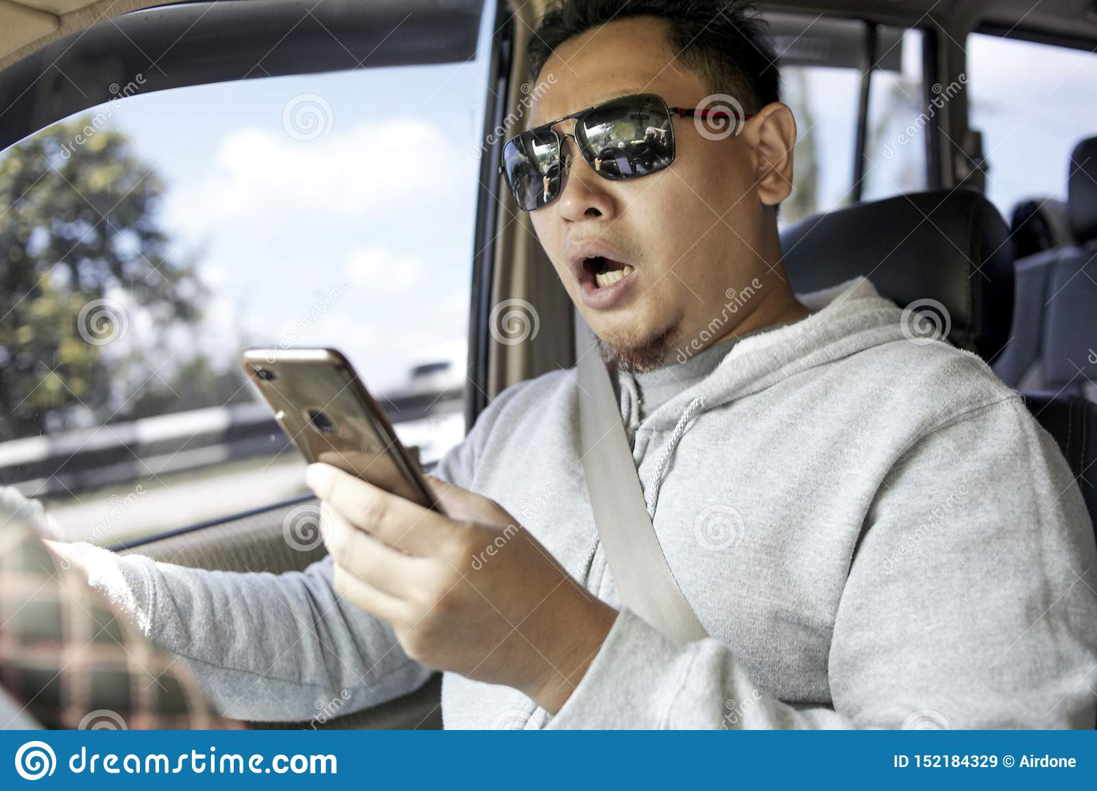 Male Driver Reading Message on Smart Phone While Driving a Car