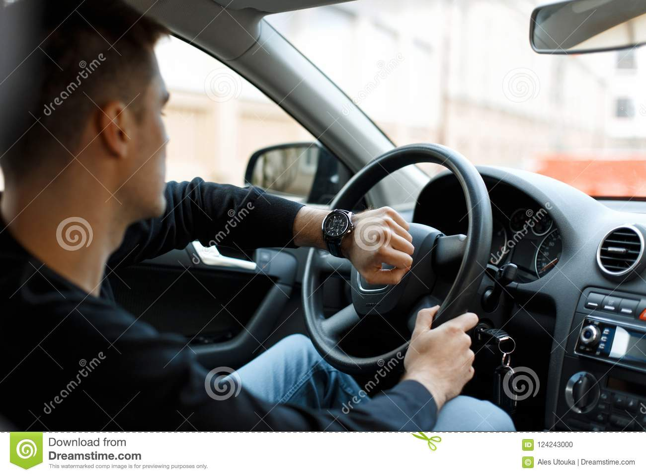 Male driver sitting in car in traffic jam and looking at clock.