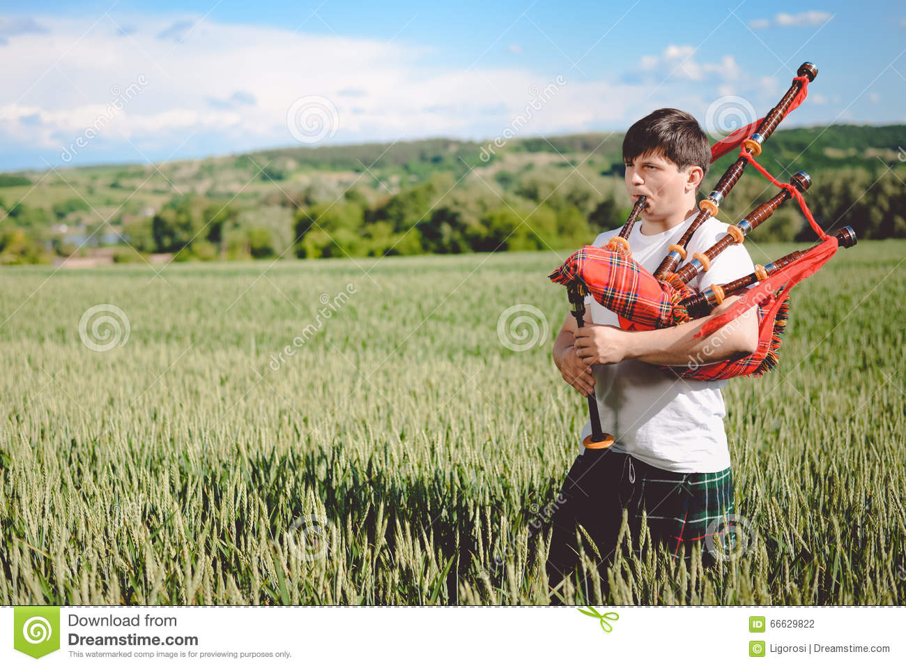 Male enjoying playing pipes in traditional kilt on green outdoors copy space summer field.