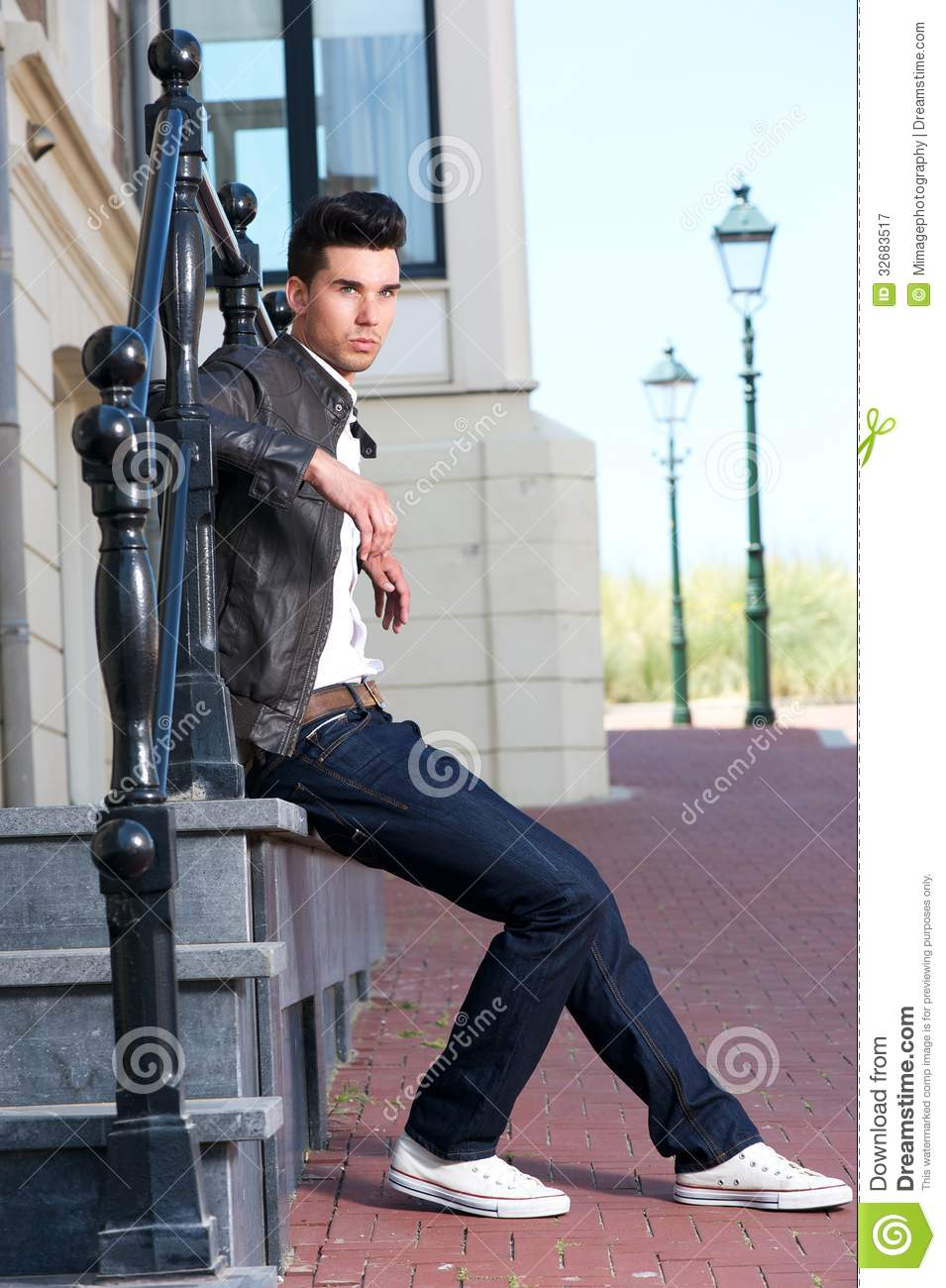 Male Fashion Model In Leather Jacket Sitting Outdoors Stock Photo