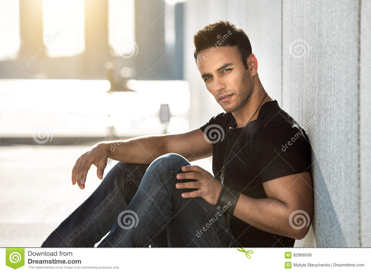 Black t shirt with dark blue jeans - Male Fashion Model Man In Black T Shirt Dark Blue Jeans And Leather Bracelet Posing Outdoors