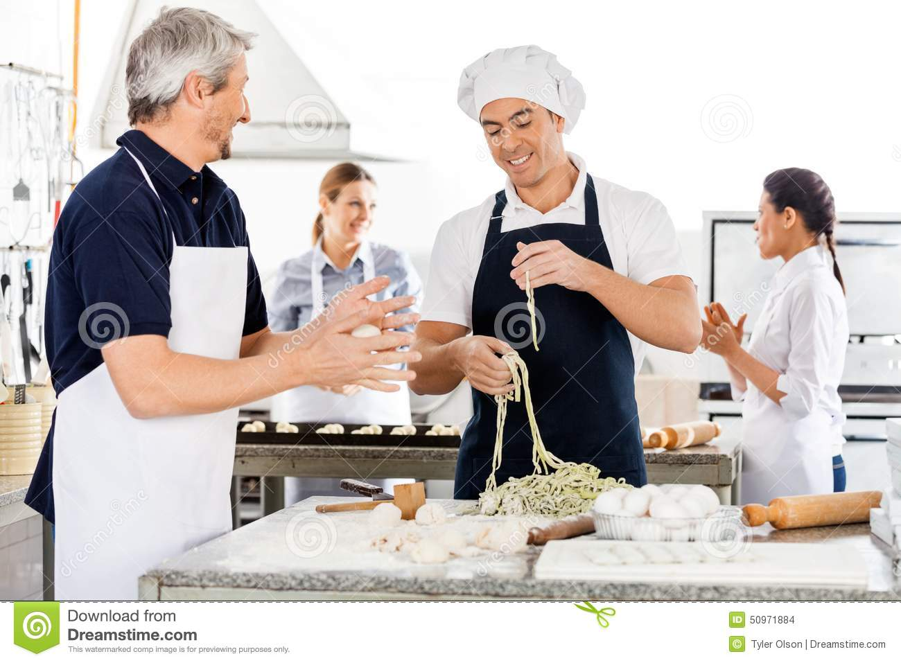 Male And Female Chefs Preparing Pasta In Kitchen