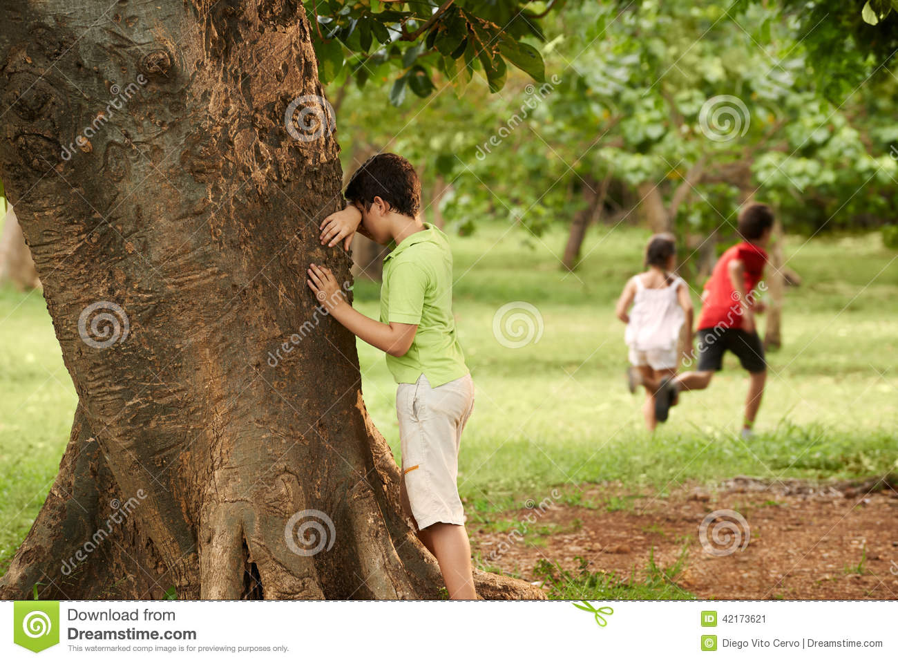 male and female children playing hide and seek stock photo