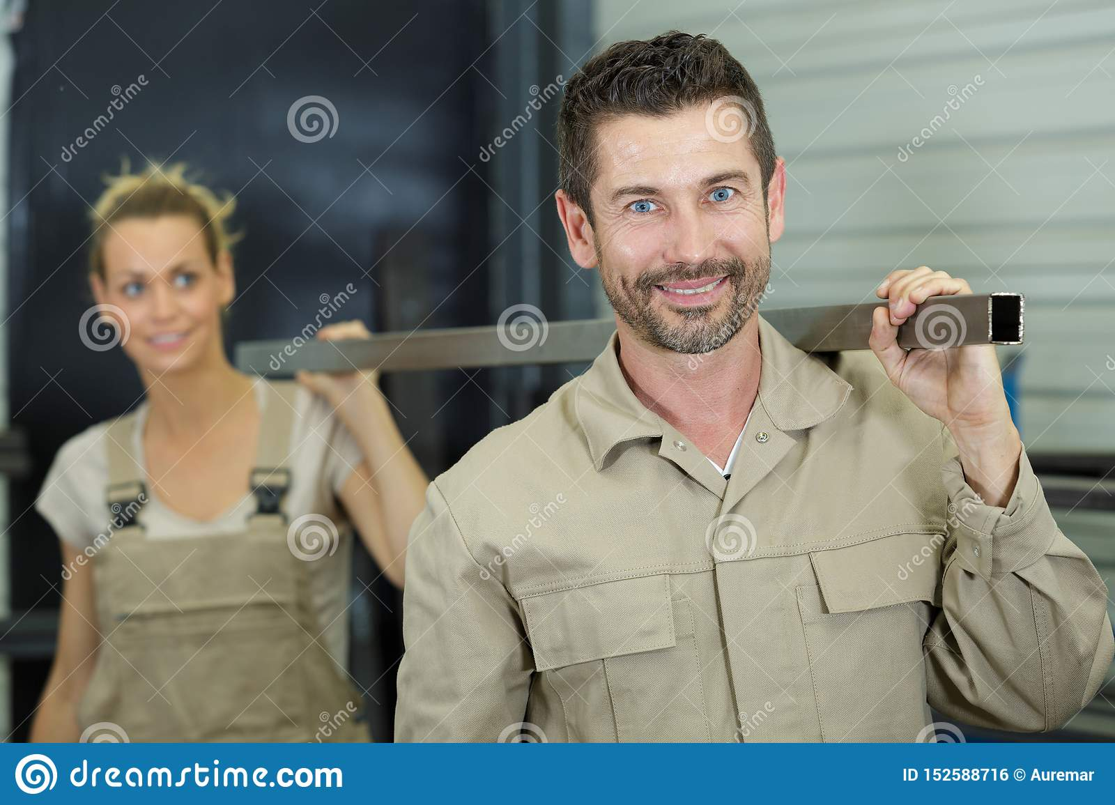 Male and female colleagues carrying metal length on their shoulders