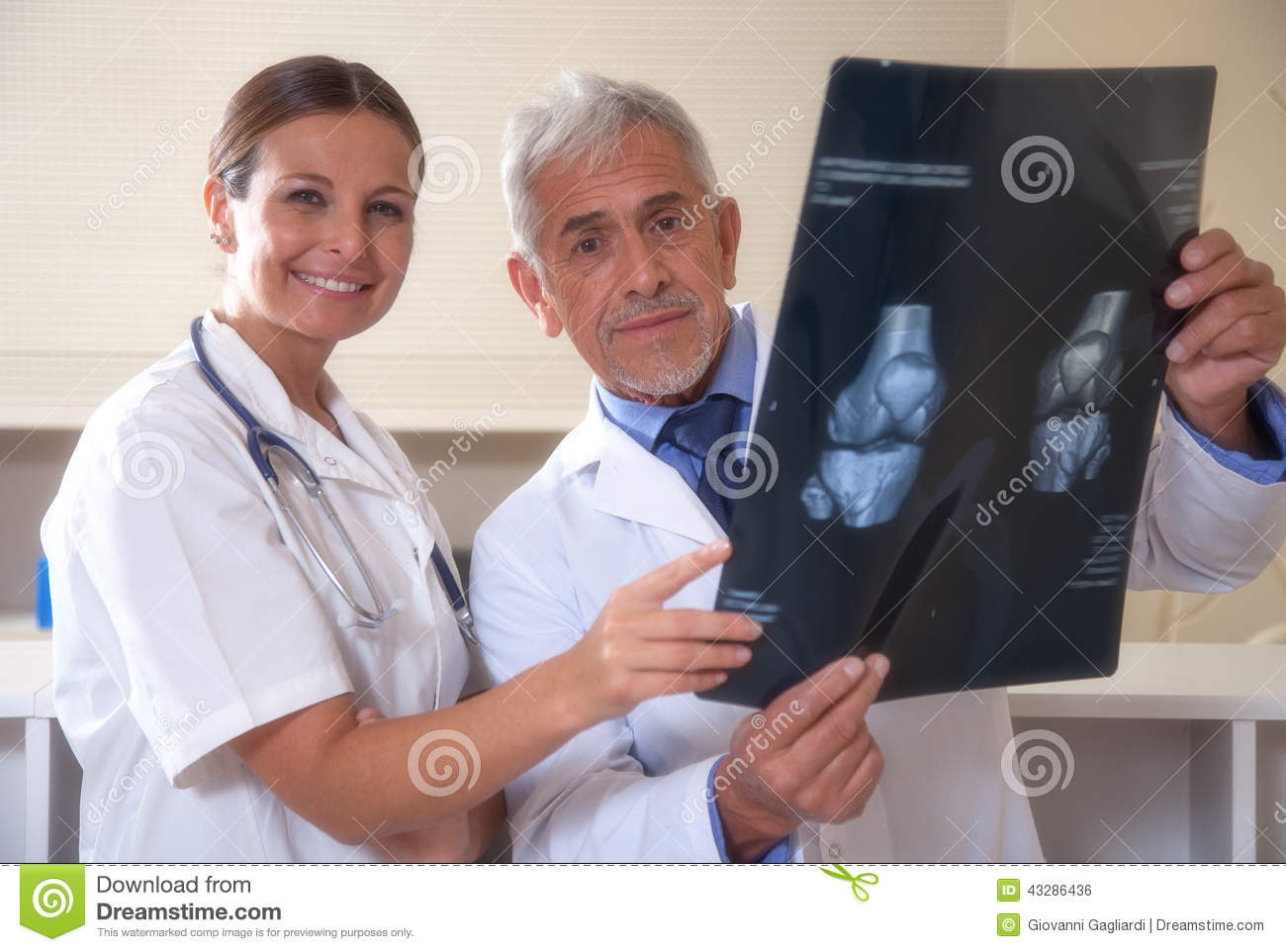 Male and female doctors smiling examining x-ray test results.