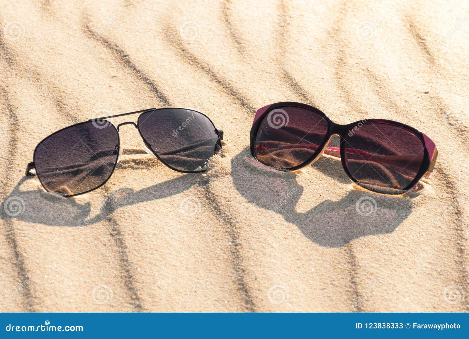 Male and female glasses on sandy beach.