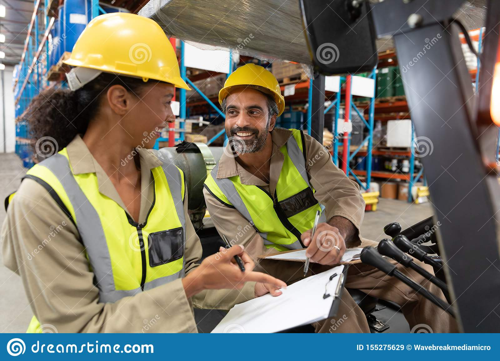 Male and female staff discussing over clipboard in warehouse