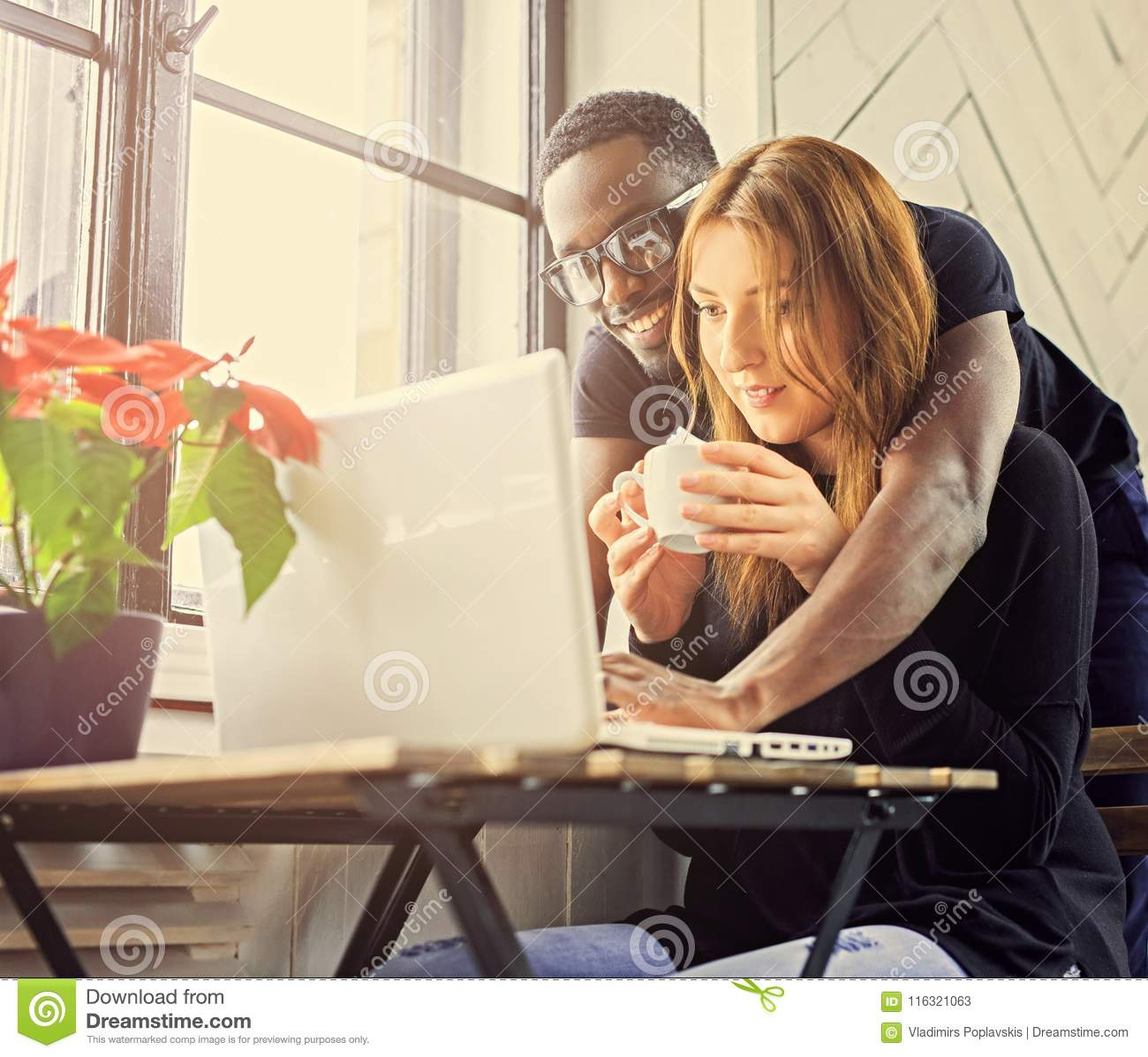 Male and female student using a laptop.