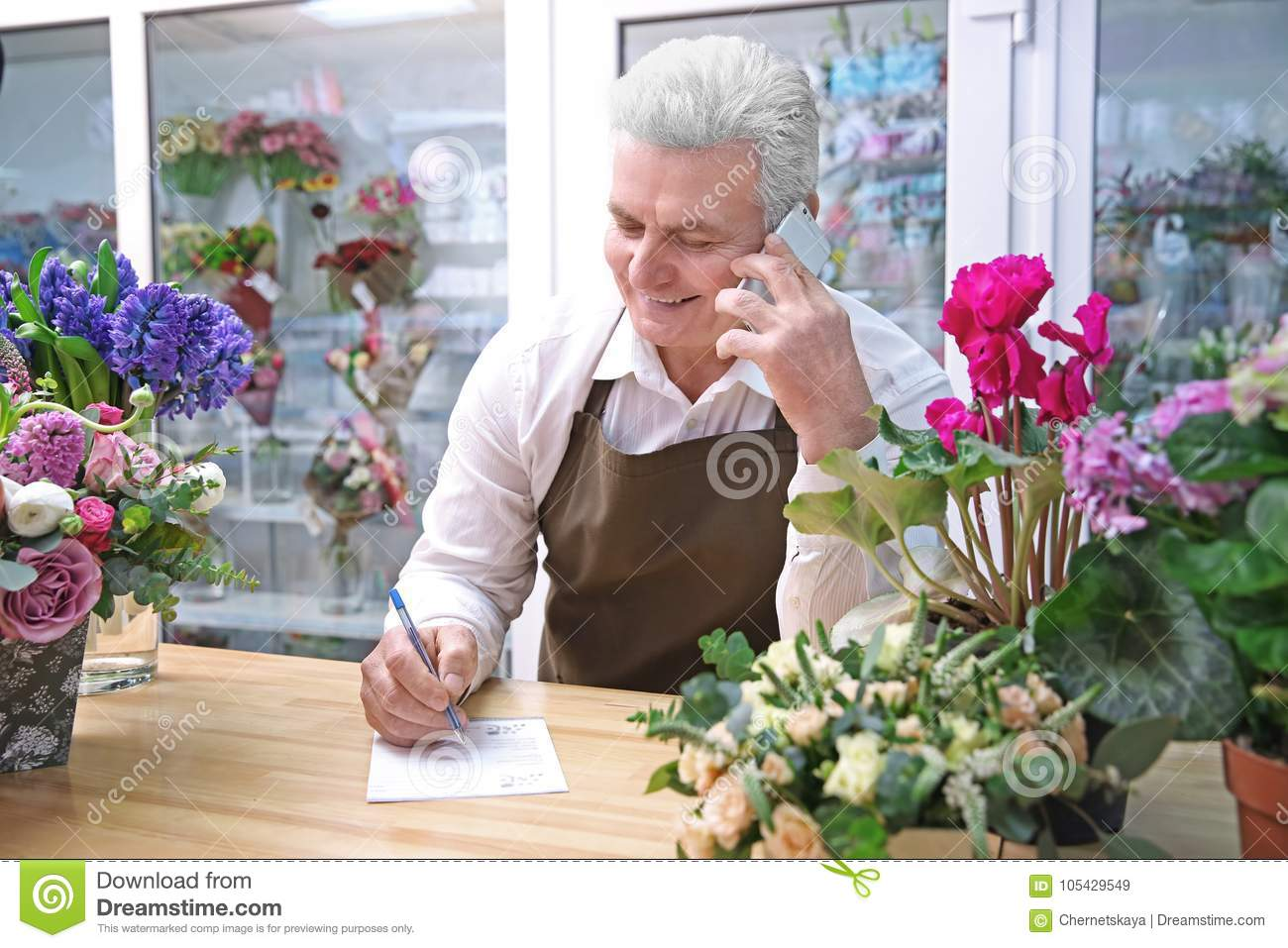 Male Florist Using Mobile Phone While Writing On Paper Stock Image