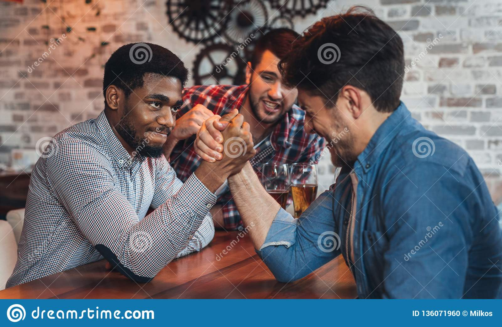 Male friends arm wrestling each other in bar