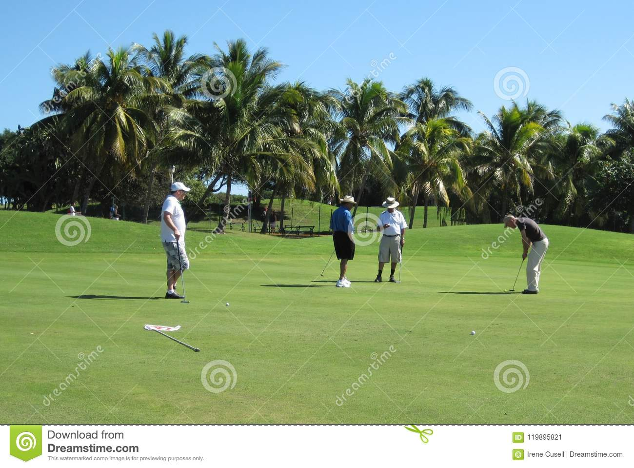 Male golf player making his putt with foursome