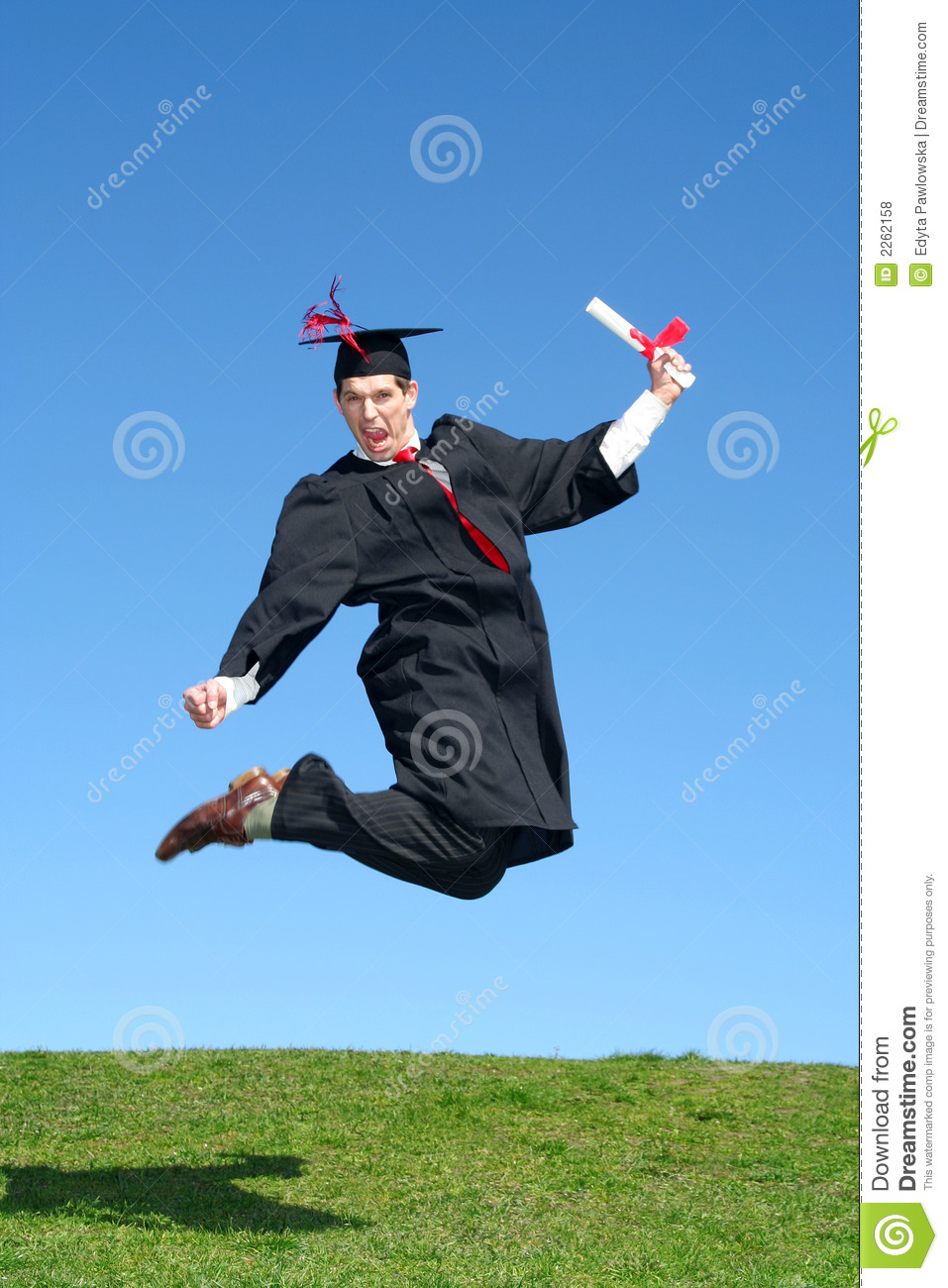 male graduate jumping for joy stock photo