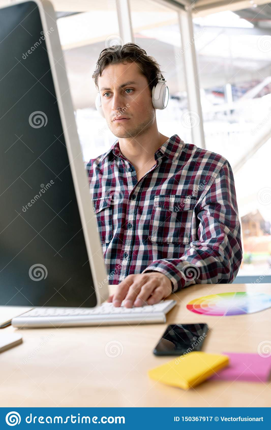 Male graphic designer listening music on headphone while working on computer at desk