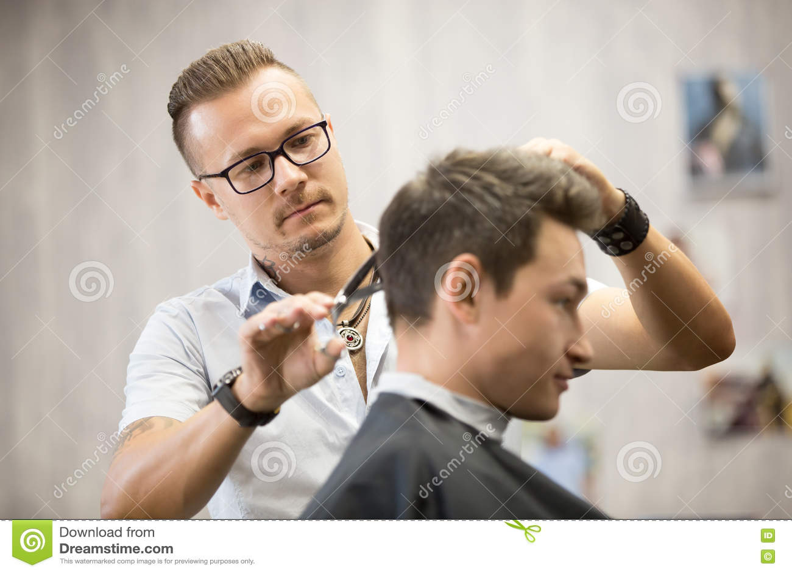 Male hairdresser making haircut