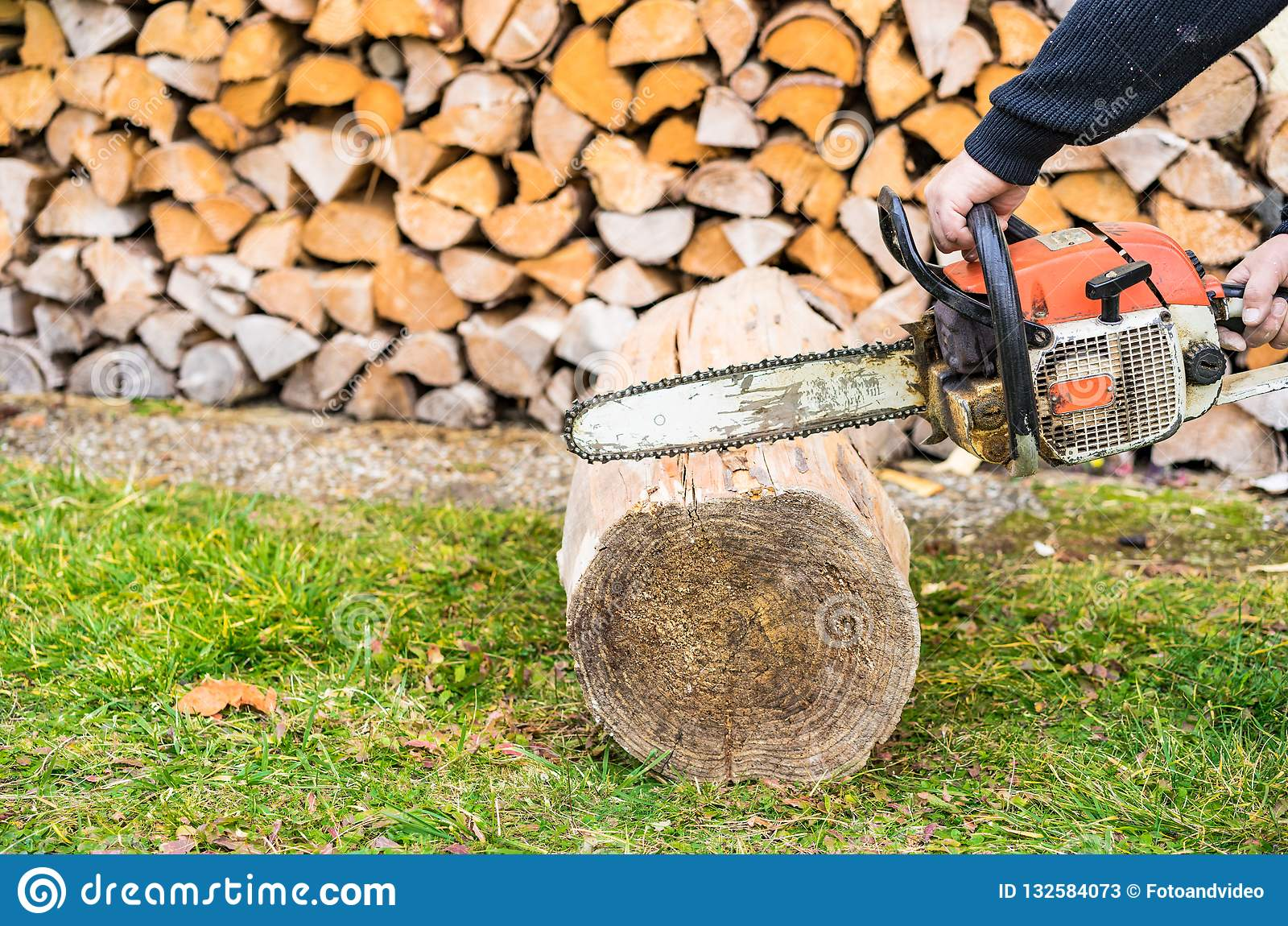 Male hand with chainsaw is cutting firewood