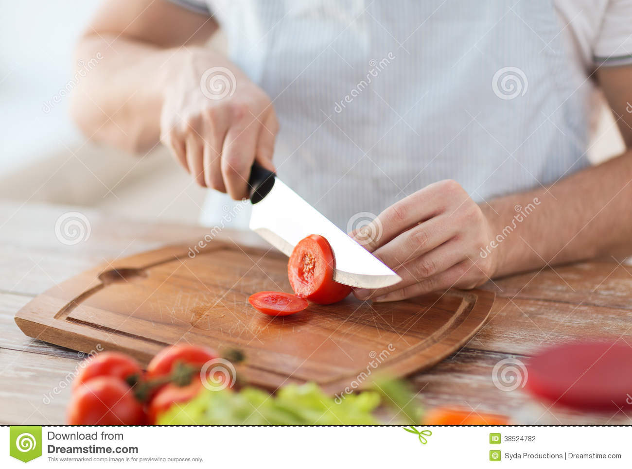 Male Hand Cutting Tomato On Board With Knife Stock Photo ...