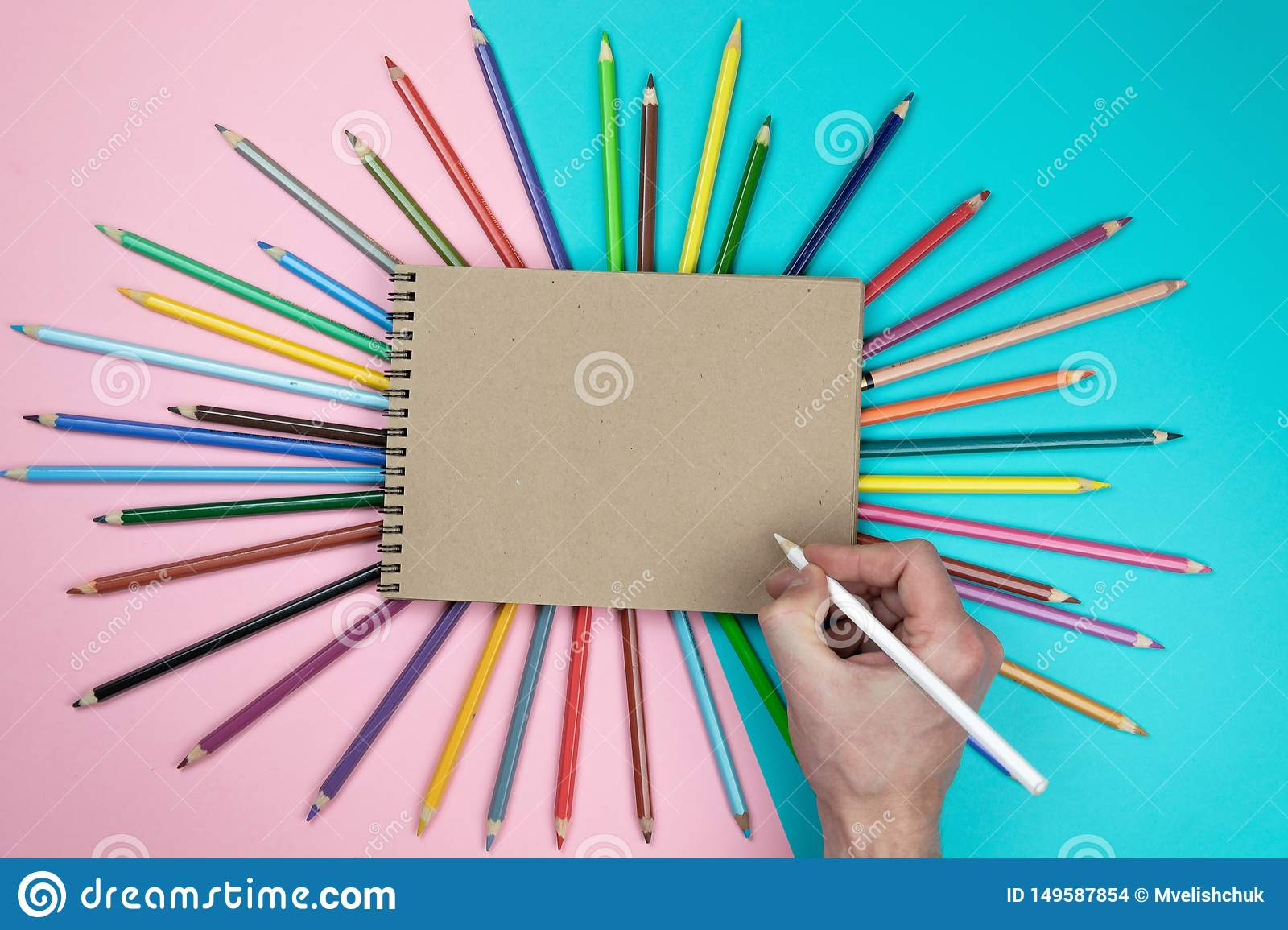 Male hand drawing, blank paper and colorful pencils. Branding stationery mockup scene, blank objects for placing your design.