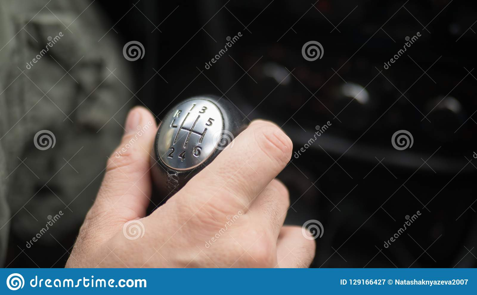 Male hand on gear lever, manual transmission.