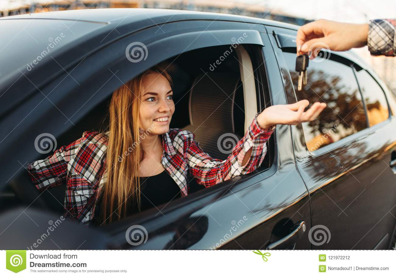 Male hand gives the car keys to female driver