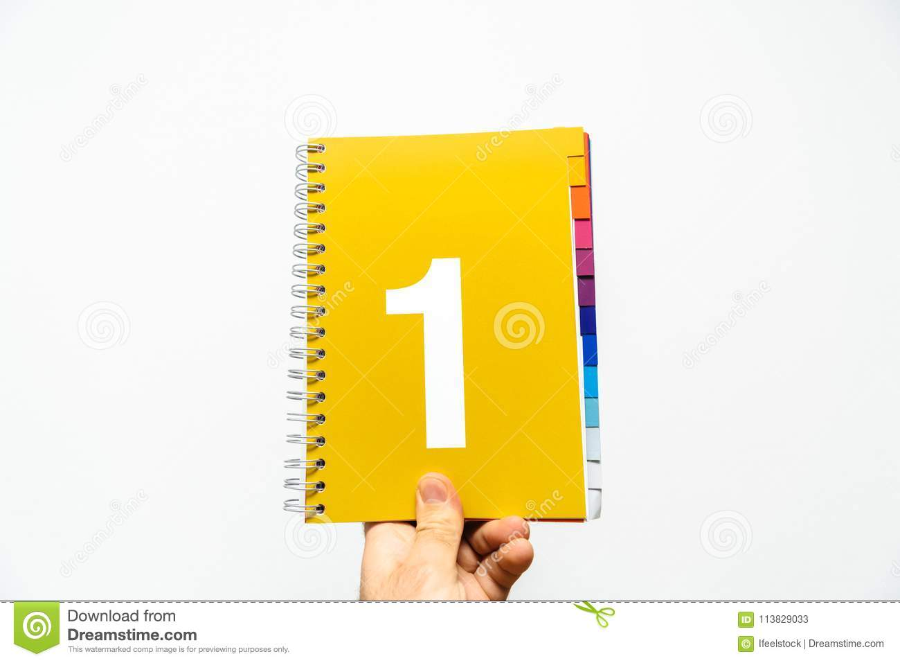 Male hand holding notebook with big number 1 on orange