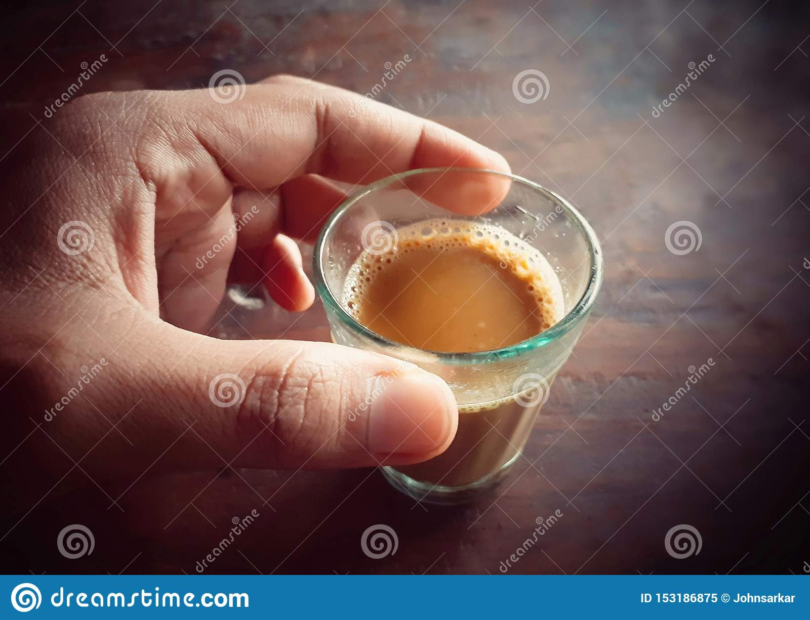 Male hand holding a small glass of tea
