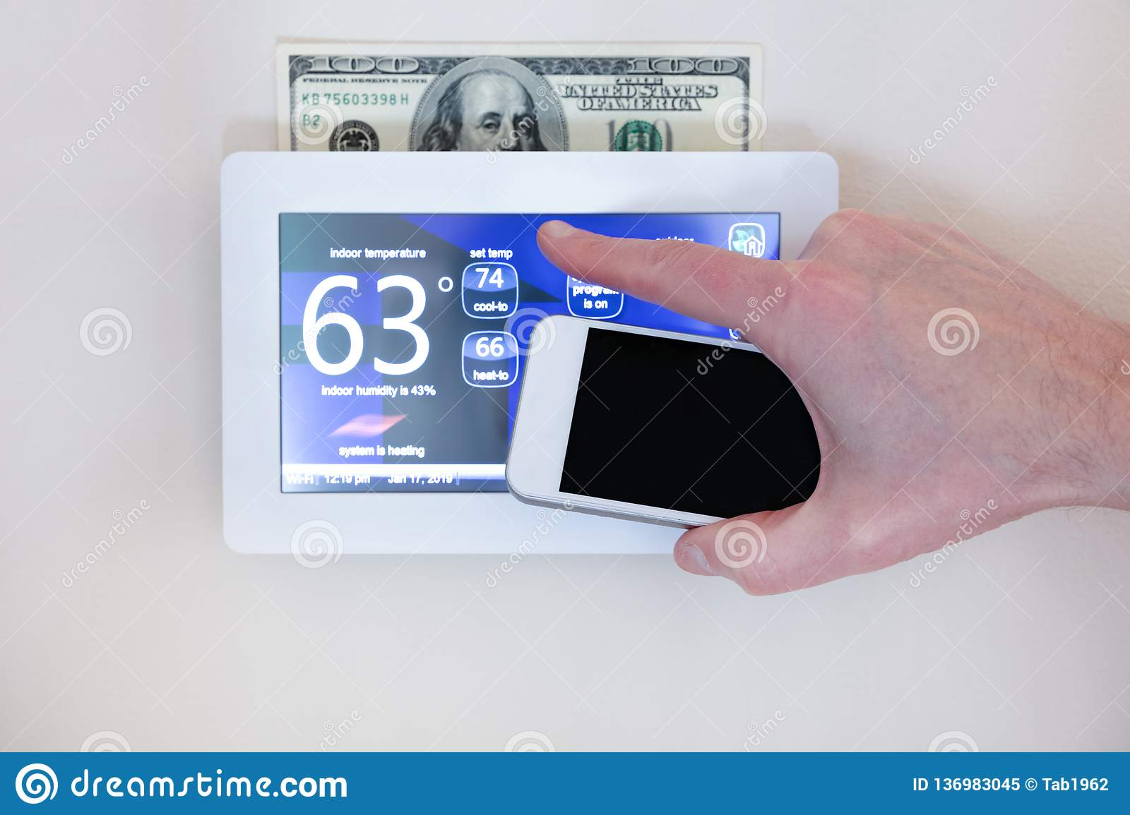 Male hand holding smart phone to operate heating or cooling via digital touch screen thermostat for home energy savings