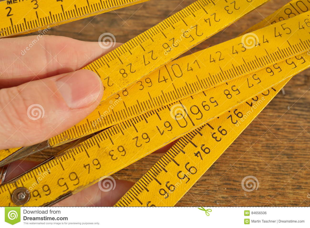 Male hand holding yellow folding meter on the wooden background as a symbol of precision