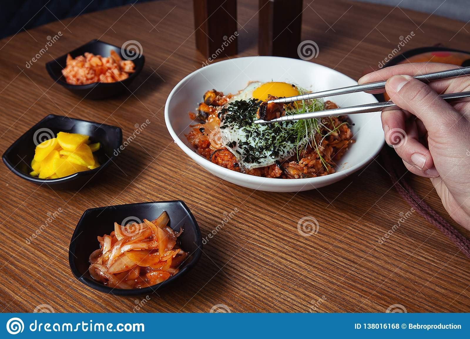 Male Hand Holds Chinese Food With Chopsticks Stock Photo