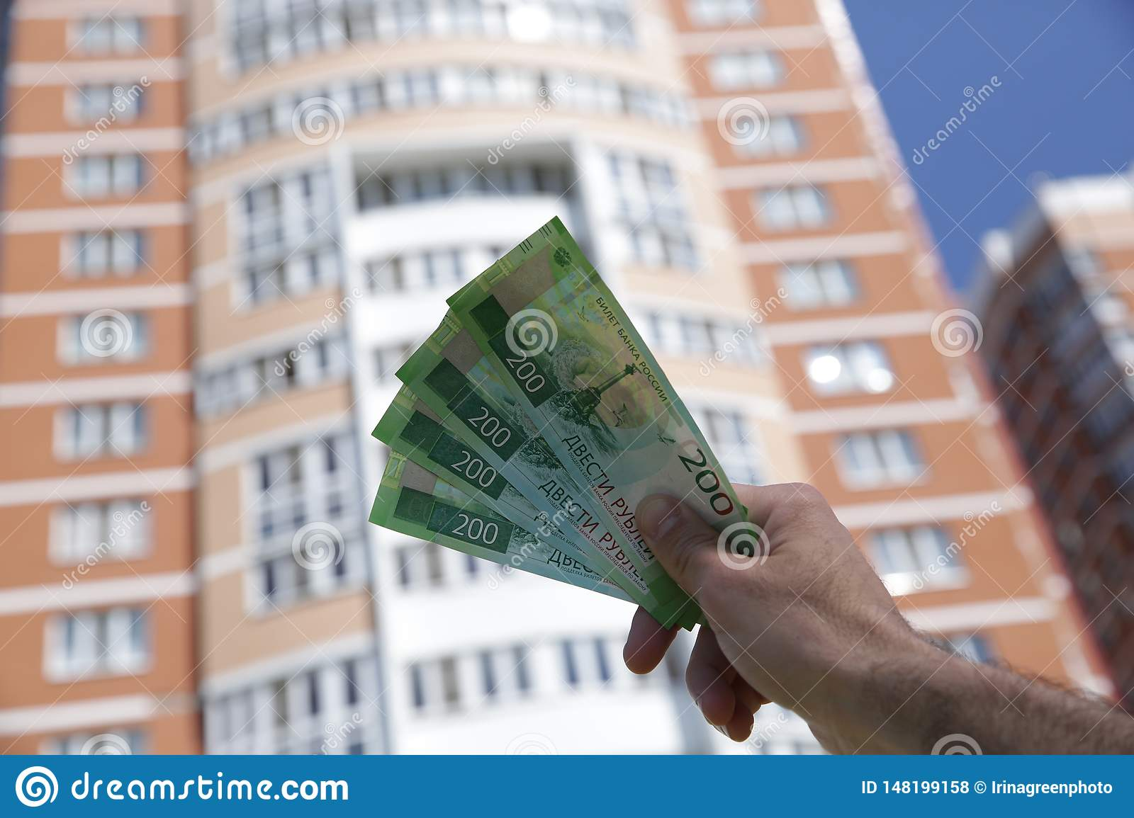 Male hand holds a new Russian banknote two hundred rubles on the background of a big building and blue sky. Cash paper money