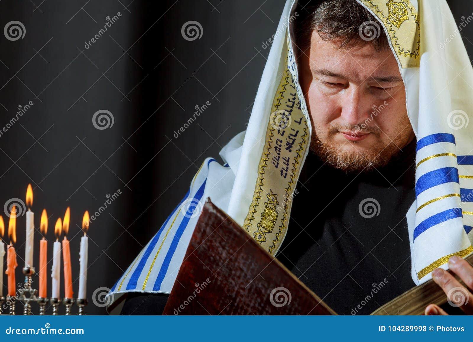 Male hand lighting candles in menorah on table Hanukkah