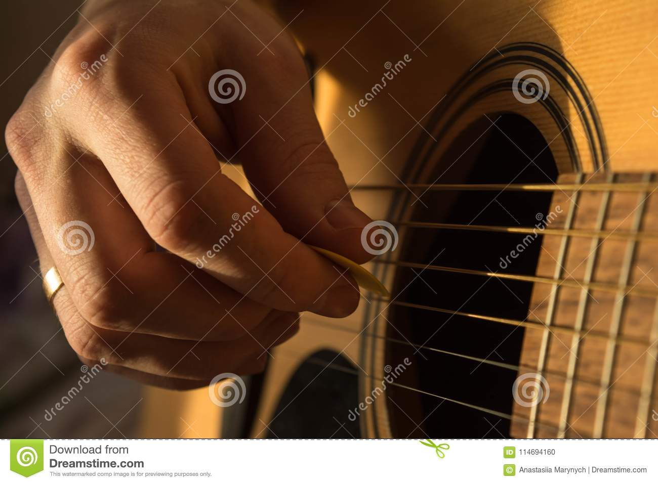 Male hand playing acoustic guitar in natural light