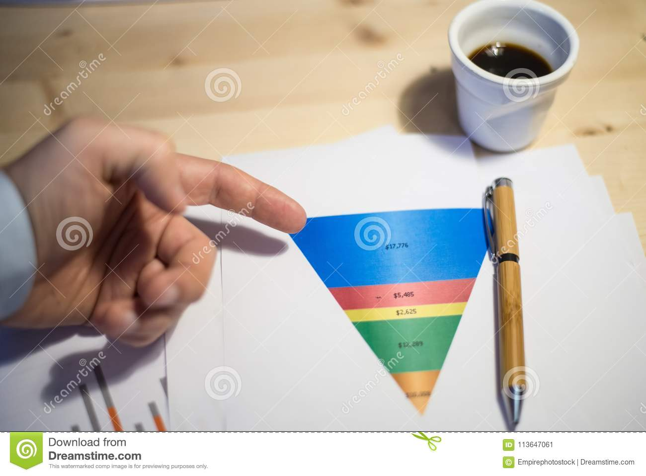 Male hand pointing at a sales funnel printed on a white sheet of paper during a business meeting