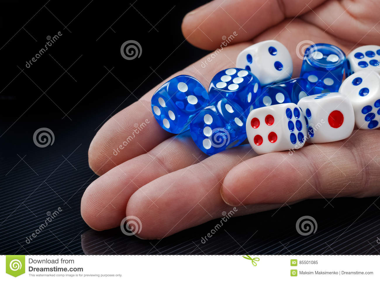 The male hand throwing dices on dark background