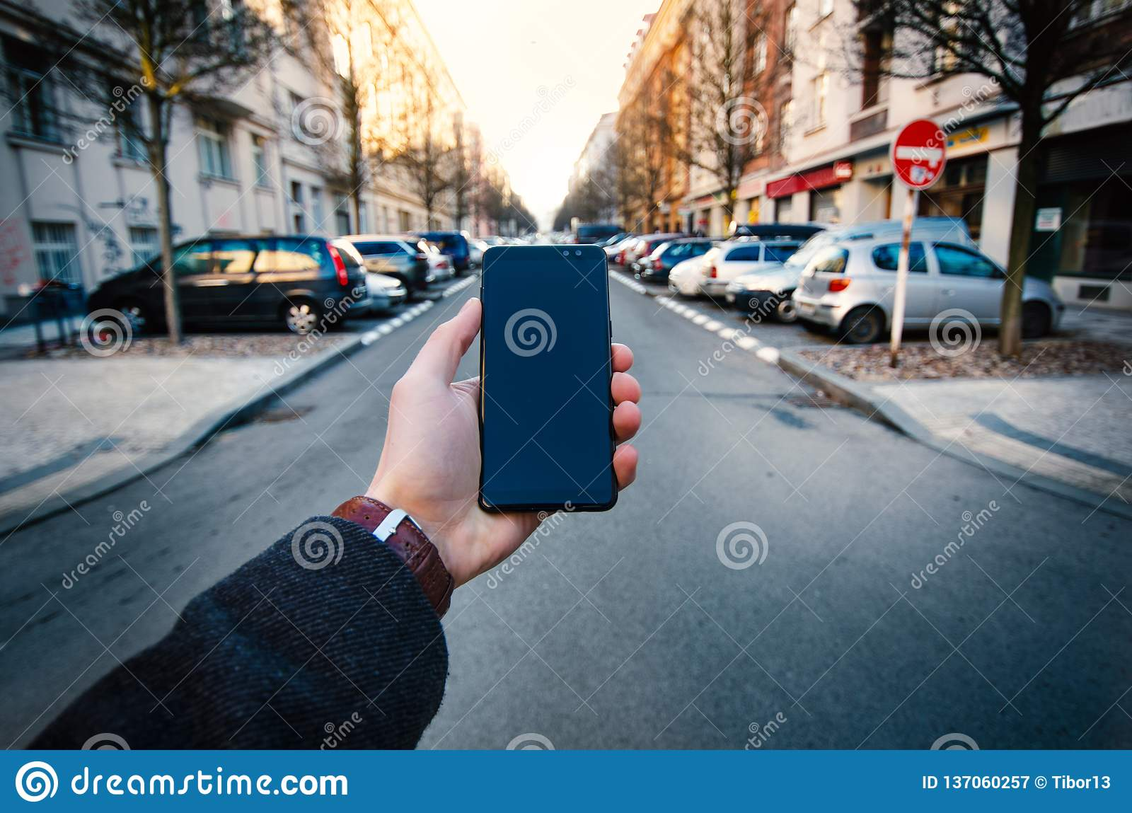 Male hand using smart phone on the street. Concept of technology and social network. Business man with watches, coat and take a ph