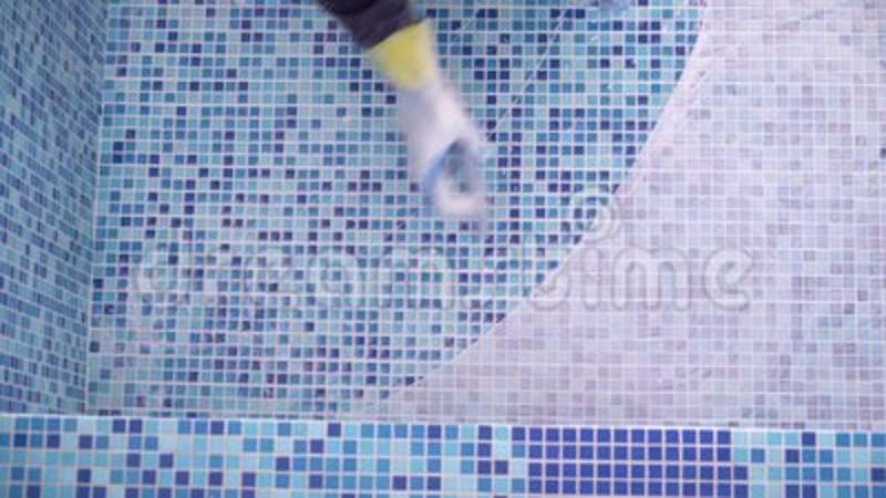 Male hand wipes dirty tile adhesive in swimming pool. Finishing off a  tiling job with wiping off grout.