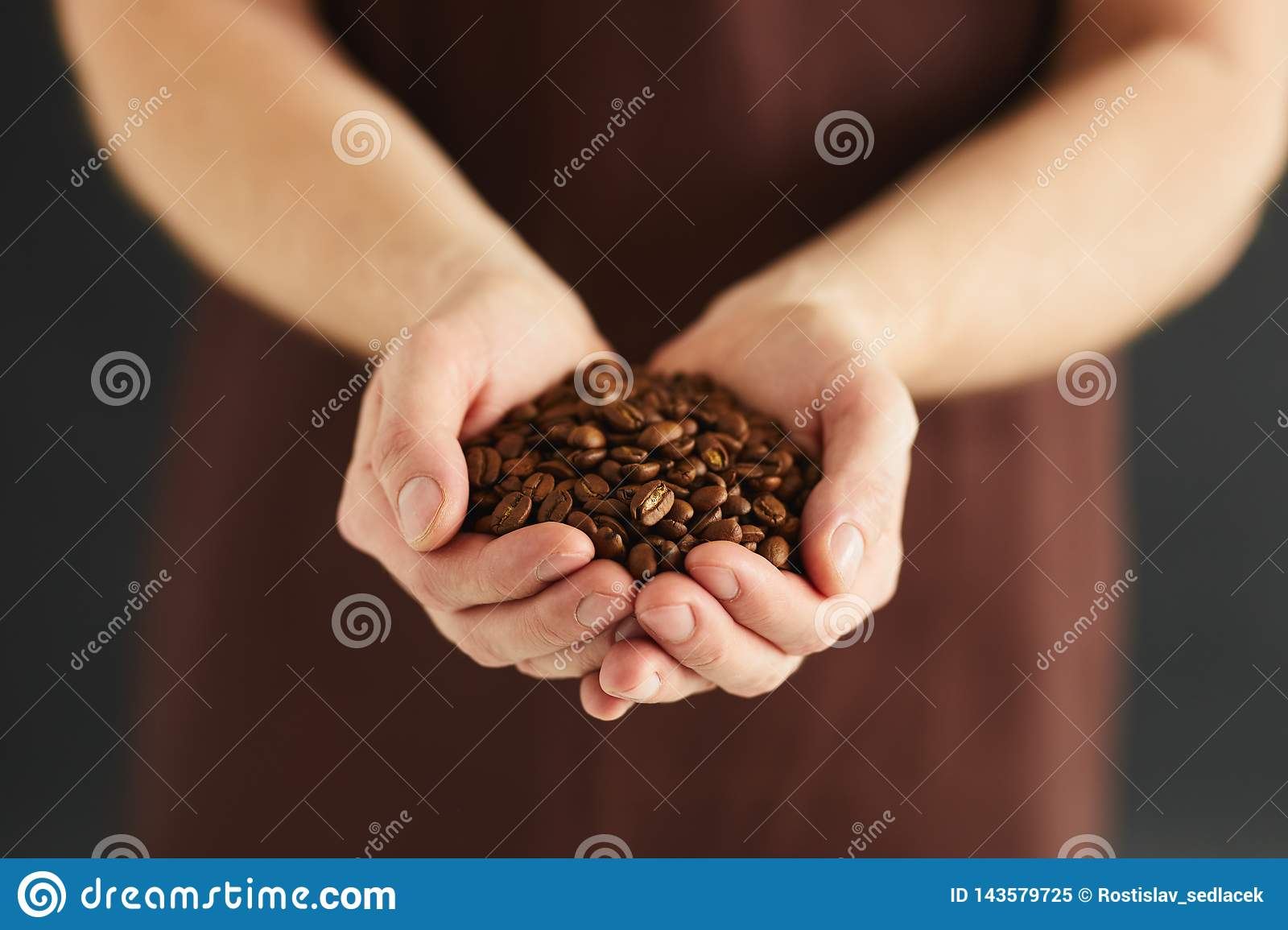 Man with a handful of coffee beans
